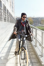 Young man riding a bicycle in the urban landscape Stock Images
