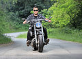Young man riding a chopper on a road Royalty Free Stock Photos