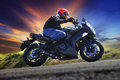 Young man riding motorcycle on curve of asphalt country road Royalty Free Stock Photo