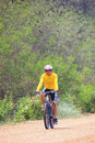 Young man riding mountain bike in dusty road use for sport leisu leisure and healthy activities Stock Photos