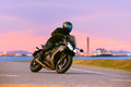 Young man riding sport touring motorcycle on asphalt highways ag Royalty Free Stock Photo