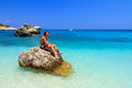 Young man on a rock handsome sits in the sea in summer the greek island zakynthos Stock Image