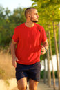 Young man running with earphones outside portrait of a Stock Photography
