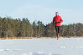 Young man running outdoors in winter snowy sunny forest Royalty Free Stock Photo