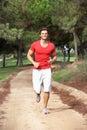 Young man running through park Stock Photo