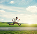 Young man running violently on the background of green meadow Royalty Free Stock Photo