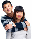 Young man's arms around young asian woman Royalty Free Stock Images