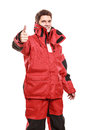 Young man sailor in red wind jacket sailing wearing waterproof showing thumb up success hand sign gesture isolated on white Royalty Free Stock Images