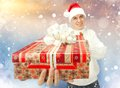 Young man in santa claus hat holding a gift box portrait of handsome big red Royalty Free Stock Photos