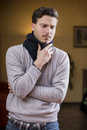 Young man with scarf, holding his neck because of throat ache Royalty Free Stock Image