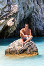 Young man in the sea handsome sits on a rock summer on greek island zakynthos Royalty Free Stock Photo