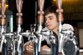 Young man seated at a bar drinking view between the stainless steel beer taps behind the counter of alone Royalty Free Stock Photo
