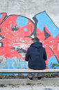 Young man seen from the back looking at a graffiti Stock Photo