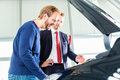 Young man and seller with auto in car dealership or salesman client or customer presenting the engine performance of new used cars Stock Images
