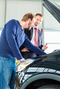 Young man and seller with auto in car dealership or salesman client or customer presenting the engine performance of new used cars Royalty Free Stock Photography