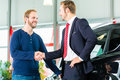 Young man and seller with auto in car dealership or salesman customer they shaking hands seal the purchase of the or new Royalty Free Stock Photo
