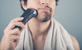 Young man shaving half of his beard a is off Royalty Free Stock Photos