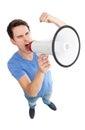 Young man shouting through megaphone Stock Images