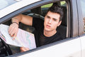 Young Man showing map inside of a car Royalty Free Stock Photo