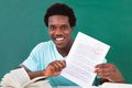 Young man showing a paper with grade a plus happy african male student perfect in classroom Royalty Free Stock Image