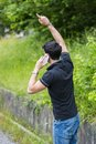 Young man on side of a road, calling and waiting Royalty Free Stock Photo
