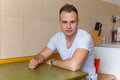 Young man siiting in the kitchen he is happy Stock Image