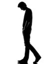 Young man silhouette sad walking