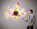 Young man singing and listening to music with musical notes getting out of his mouth Royalty Free Stock Photos