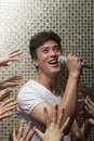 Young man singing into a microphone with lots of hands reaching for him men Royalty Free Stock Image