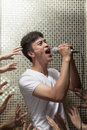 Young man singing into a microphone with lots of hands reaching for him men Royalty Free Stock Images