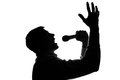 A young man singing into a microphone raising his hands silhouette Royalty Free Stock Photo
