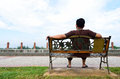 Young man sit on the bench at park Stock Photography
