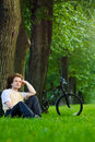 Young man siting under the tree near his bycicle Royalty Free Stock Images