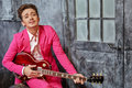 Young man sits on armchair and plays guitar in pink suit semiacoustic Royalty Free Stock Photography