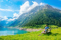 Young man sits on bench by mountain lake, Austria Royalty Free Stock Photo