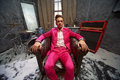 Young man sits in dusk in old armchair pink suit with air of detachment Royalty Free Stock Photo