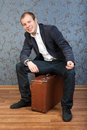 A young man sits on an old suitcase Royalty Free Stock Photo