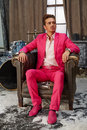 Young man sits in scuffed old armchair pink suit room powdered with snow drum set is behind his back Royalty Free Stock Photography