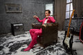 Young man sits in scuffed old armchair in room pink suit powdered with snow Stock Photo