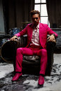 Young man sits in semidarkness in old armchair pink suit with air of detachment Royalty Free Stock Images