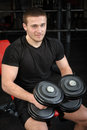 Young man sits after workout in gym Stock Images