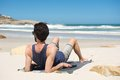 Young man sitting alone at an secluded beach rear portrait of a Royalty Free Stock Image