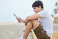 Young man sitting on beach reading ebook Royalty Free Stock Photo