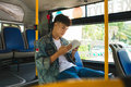 Young man sitting in city bus and reading a book. Royalty Free Stock Photo