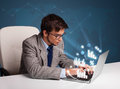 Young man sitting at desk and typing on laptop with diagrams and graphs comming out Royalty Free Stock Images
