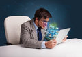 Young man sitting at desk and watching his photo gallery on lapt attractive laptop Royalty Free Stock Image