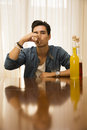 Young man sitting drinking alone at a table with two bottles of liquor alongside him sipping from shot glass to drown his sorrows Stock Photography