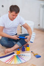 A young man sitting on floor holding paint roller and looking color palette Royalty Free Stock Photo