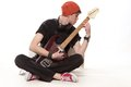 Young man sitting on floor and playing guitar in a red cap Stock Image