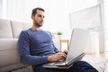 Young man sitting on floor using laptop at home in the living room Royalty Free Stock Photos